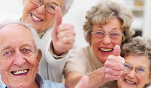 Gruppe Senioren lacht in die Kamera, zeigt den Daumen hoch.