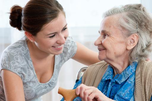 Pflegerin unterhält sich mit Seniorin.