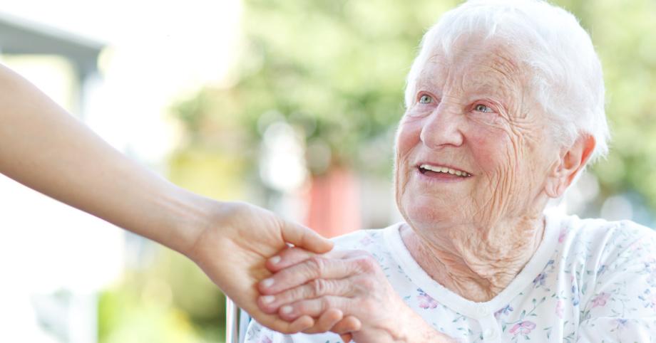 Alte Frau im Rollstuhl reicht Pflegerin die Hand und lächelt.