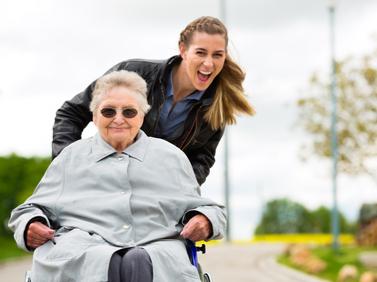 Die MediCare Pflegerin unterwegs in der Natur mit Seniorin.