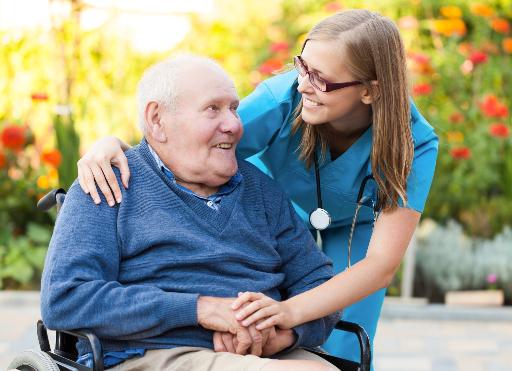 Senior im Rollstuhl wird von einer Medicare Pflegerin betreuut.