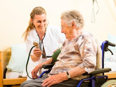 Pflegerin misst Blutdruck einer Seniorin.