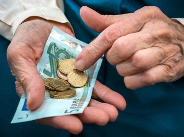 Hand mit Geld: Kostenübernahme spielt in der Altenpflege eine entscheidende Rolle.