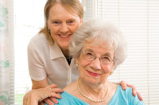 Seniorin und MediCare Pflegekraft lächeln in die Kamera.
