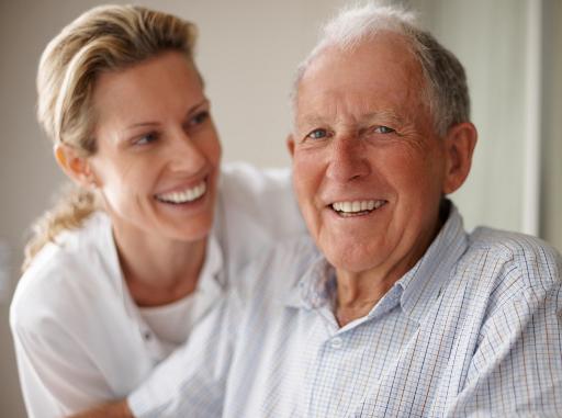 Harmonische Betreuung: Pflegerin und Senior lachen in die Kamera.